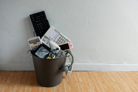 Electronic Waste broken or damage In Recycle bin in the room with white wall and leave blank space above for text input, Reuse and Recycle concept. 스톡 콘텐츠 - 139897749