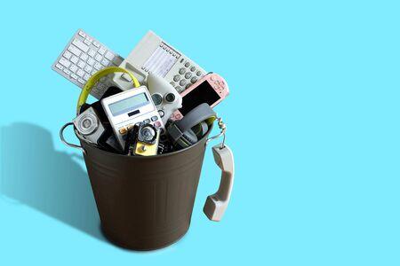 Déchets électroniques cassés ou endommagés dans la poubelle isolés sur fond bleu et laissez un espace vide au-dessus pour la saisie de texte, le concept de réutilisation et de recyclage