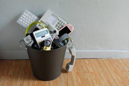 Déchets électroniques cassés ou endommagés Dans la corbeille dans la pièce avec un mur blanc et laissez un espace vide au-dessus pour la saisie de texte, le concept de réutilisation et de recyclage. Banque d'images