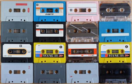 Collection of colorful old audio cassette tape on wooden background. 에디토리얼