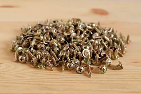 Close up of many metal screws on wooden background, Concept of construction and Industrial