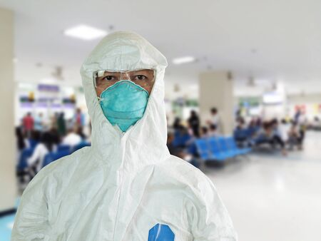 Medical personnel in half protective clothing uniform PPE suit and Surgical mask or hygienic mask N95 and blurred of hospital background, During coronavirus covid-19 outbreak, Concept of pandemic virus. 스톡 콘텐츠 - 145867371