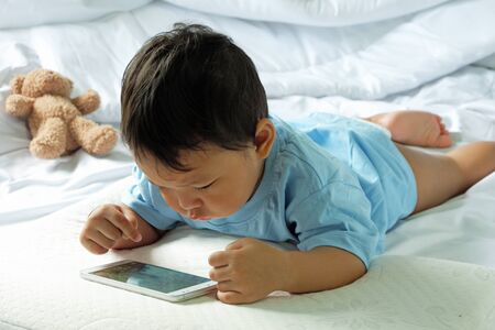 Asian boy about 2 years old, watching and playing mobile phone on the white bed