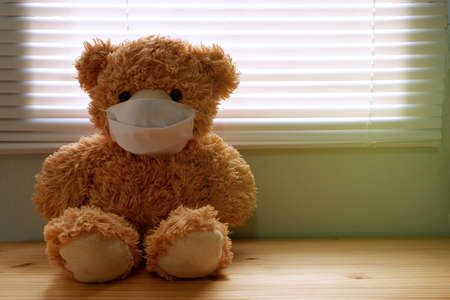 Teddy bear wearing a face mask, by the window with loneliness and Sadness. Coronavirus Covid-19 and pm2.5, stay at home, quarantine concept.