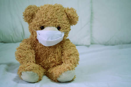Teddy bears are sick, wearing a mask, sitting on a white bed with loneliness and loneliness. Coronavirus Covid-19 and pm2.5, stay at home, quarantine concept.