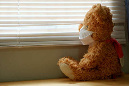 Teddy bear wearing a face mask, sitting and looking out the window with loneliness and Sadness. Coronavirus Covid-19 and pm2.5, stay at home, quarantine concept.