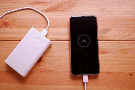 Smartphone is charging with backup battery or white power bank on the desk wooden table