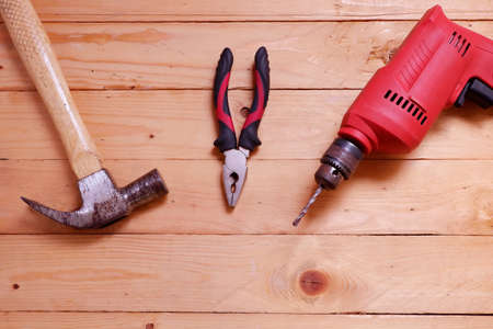 Electric drill, Wooden hammer and pliers Hand tools used on wooden table with copy space 스톡 콘텐츠