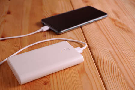 Smartphone is charging with backup battery or white power bank on the desk wooden table 스톡 콘텐츠 - 151465575