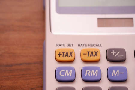 Focus the tax button on the calculator. Concept of calculation and annual tax refund.