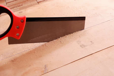 A hand saw is cutting sheet wood.
