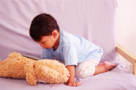 Cute asian about 2 years old, watching and playing mobile phone sits on the sofa in the living room. Ignoring the teddy bear 스톡 콘텐츠