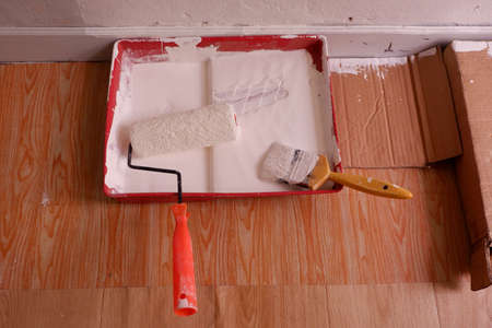 Paint roller and paint brush in the tray. The painter is doing the wall