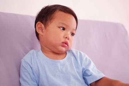 Asian boy about 2 years old with a cold, runny or sick nose, sits on the sofa in the living room.
