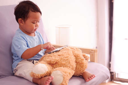 Asian boy about 2 years old watching and playing mobile phone sits on the sofa in the living room. 스톡 콘텐츠