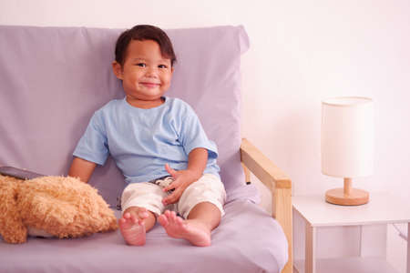 Cute asian boy about 2 years old smiling on the sofa in the living room. 스톡 콘텐츠