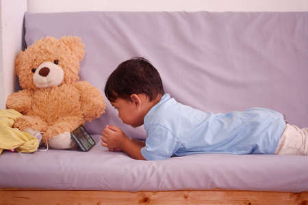 Asian boy about 2 years old, watching and playing mobile phone sits on the sofa in the living room. Ignoring the teddy bear 스톡 콘텐츠