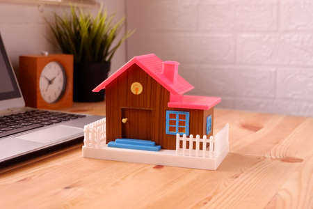 Toy house on desk with laptop computer, The concept of buying a dream home for beginners working