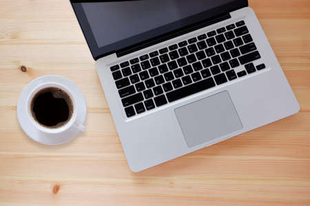 Laptop computer and black coffee in white cup on wooden desk with copy space, Top view.
