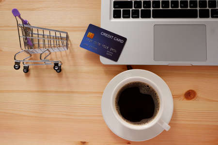 Shopping cart and credit card and laptop computer with black coffee in white cup. Concepts of online shopping or delivery where consumers can buy products directly from home or work. 스톡 콘텐츠