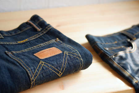 Jeans trousers stacked on wooden background with copy space for text design 스톡 콘텐츠
