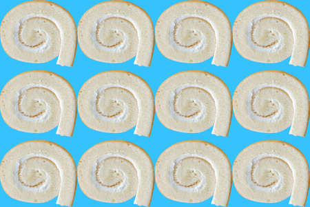 Plenty of delicious buttercream roll cakes lined up in patterns on a blue background. 스톡 콘텐츠