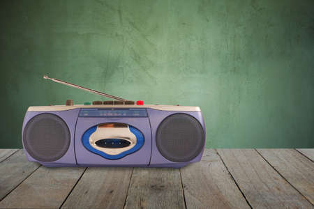 Blue radio cassette tape recorder with antenna on wooden floor and old cement wall background.