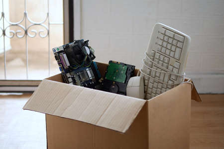 Old hard disk dive and motherboards and used keyboard with mouse old computer hardware accessories in paper boxes, Obsolete equipment is electronic waste Reuse and Recycle concept.
