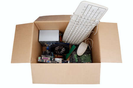 Old hard disk dive and motherboards and used keyboard with mouse old computer hardware accessories in paper boxes isolated on white