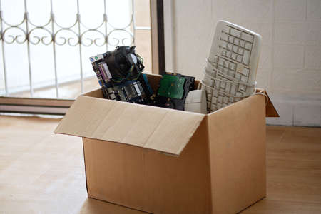 Old hard disk dive and motherboards and used keyboard with mouse old computer hardware accessories in paper boxes