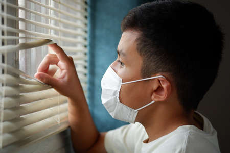 Asian boys wearing a face mask, and looking out the window with loneliness and Sadness.   pm2.5, stay at home, quarantine concept.