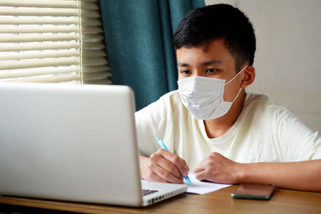 Asian boy wearing face mask and looked at laptop computer to study online, Online education via the internet during the   epidemic, stay at home, quarantine concept. 스톡 콘텐츠