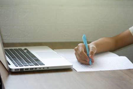 ็Hand of an Asian boy is writing book or studying online on the internet. during the  epidemic, stay at home, quarantine concept.