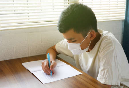 Asian boys cover their faces with masks and write or do homework during the outbreak at home. Stockfoto