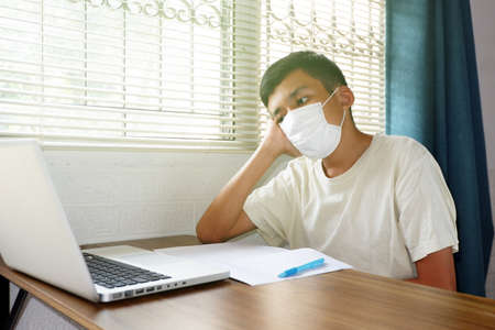 Asian boy wearing face mask and looked at laptop computer to study online, Bored with online education via the internet during the epidemic, stay at home, quarantine concept. 스톡 콘텐츠