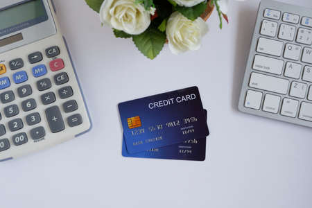 Credit card on computer keyboard with calculator and flowerpot on white desk. Concept of Online shopping and payment.