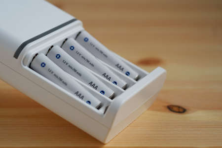 Selective focus rechargeable AAA battery in a white charger on wooden background. 스톡 콘텐츠