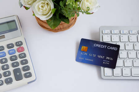 Credit card on computer keyboard with calculator and flowerpot on white desk, with copy space for text. Concept of Online shopping and payment.