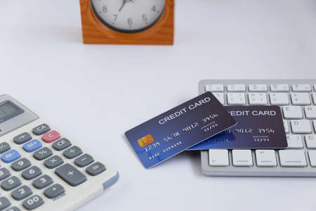 Credit card on computer keyboard with calculator and table clock on white desk. Concept of Online shopping and payment. Stockfoto