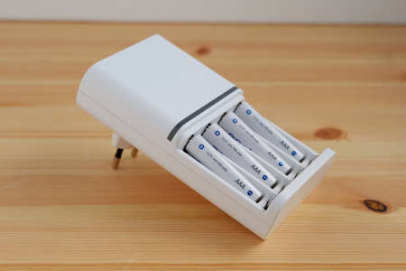 Rechargeable AAA battery in a white charger on wooden background.