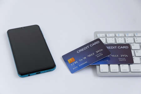 Credit card on computer keyboard with smartphone on white desk. Concept of Online shopping and payment.