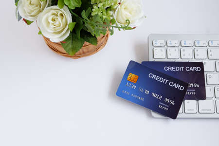 Credit card on computer keyboard and flowerpot on white desk. with copy space for text. Concept of Online shopping and payment.