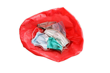 Disposable face mask in red bag for biohazards waste isolated on white background. So that the pathogen does not spread