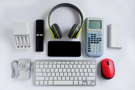 Smartphone with Headphones and Scientific calculator and other electronic gadgets on White background, Reuse and Recycle concept, Top view.