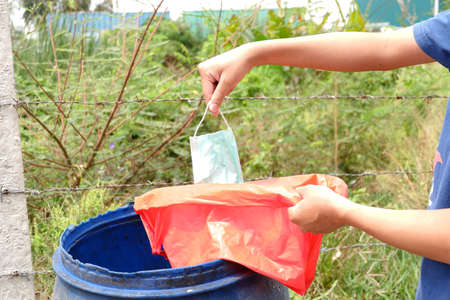Man throwing a disposable face mask in red bag for biohazards waste. So that the pathogen does not spread