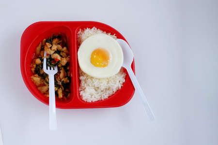 Spicy basil chicken with fried egg on steamed rice in red plastic box, disposable plastic containers. ready to eat 스톡 콘텐츠