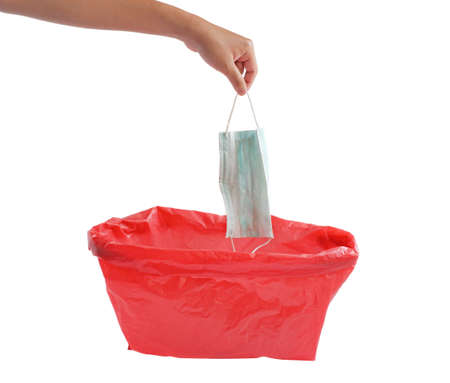 Man throwing a disposable face mask in red bag for biohazards waste isolated on white background. So that the pathogen does not spread Banco de Imagens
