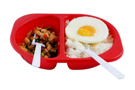 Spicy basil chicken with fried egg on steamed rice in red plastic box, disposable plastic containers isolated on white background. ready to eat