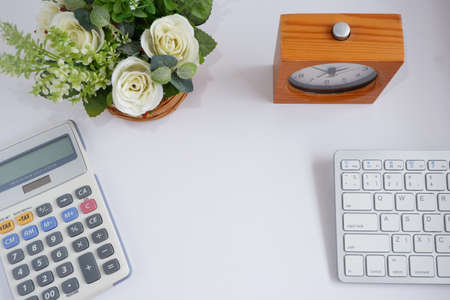 Computer keyboard with calculator and flowerpot on white desk, with copy space for text.