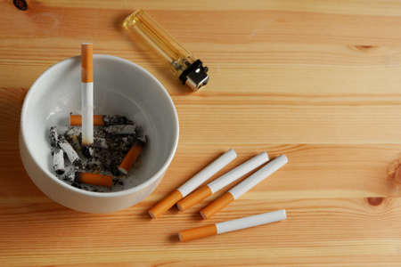 Many cigarette with white ashtray and lighter on wooden table 스톡 콘텐츠